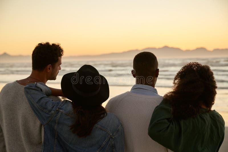 Groupe d'amis sur le lever de soleil de observation de plage d'hiver ensemble photographie stock libre de droits