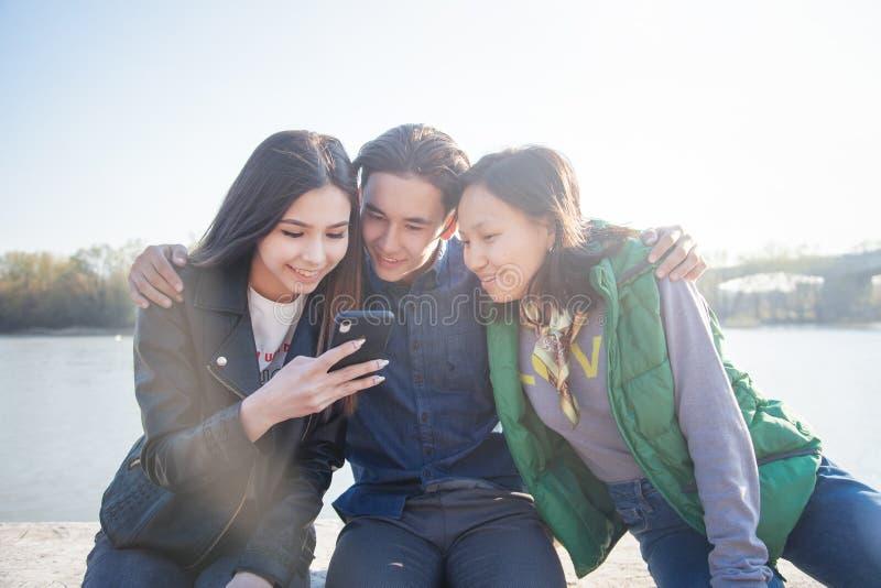Groupe d'ann?es de l'adolescence asiatiques ? la mode avec le t?l?phone portable dehors, ayant l'amusement, g?n?ration num?rique photos stock