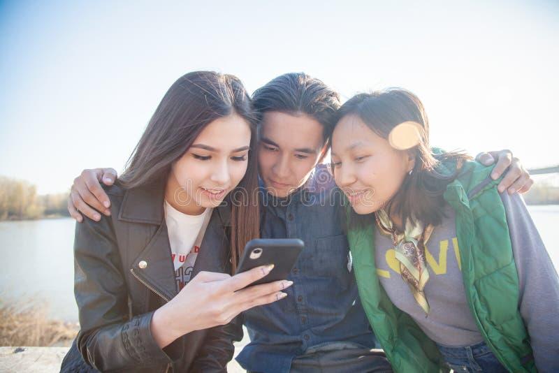 Groupe d'ann?es de l'adolescence asiatiques ? la mode avec le t?l?phone portable dehors, ayant l'amusement, g?n?ration num?rique images stock