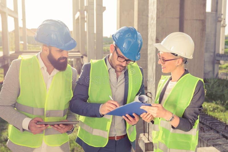 Groupe d'architectes ou d'associés ayant une réunion et signant des documents sur un chantier de construction photographie stock libre de droits
