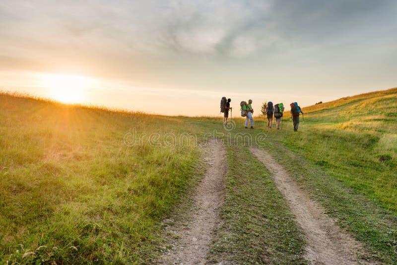 Groupe d'augmenter des amis dans les montagnes de coucher du soleil photographie stock