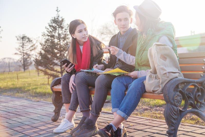 Groupe d'?coliers adolescents asiatiques d'?tudiants s'asseyant sur un banc en parc et pr?parant des examens photographie stock