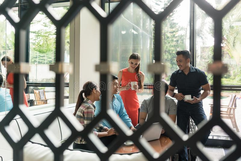 Groupe d'employés gais buvant du café dans le secteur de salon images stock