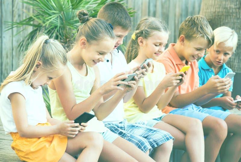 Groupe d'enfants amicaux jouant avec des téléphones portables dehors photo stock