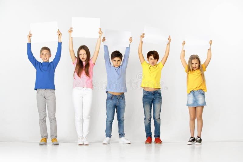 Groupe d'enfants avec bannières blanches d'isolement dans le blanc photographie stock