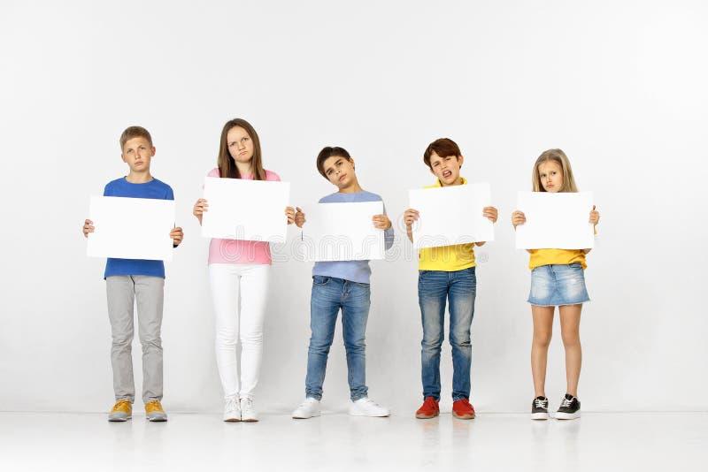 Groupe d'enfants avec bannières blanches d'isolement dans le blanc photographie stock libre de droits