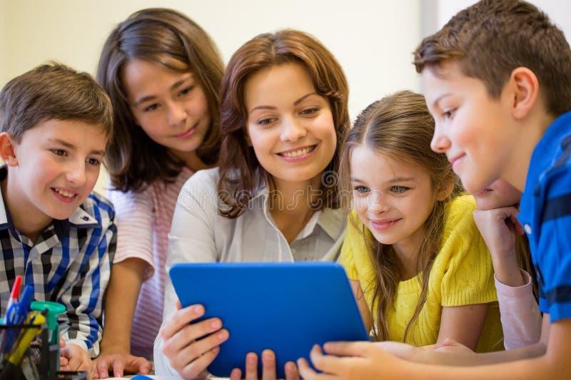 Groupe d'enfants avec le PC de professeur et de comprimé à l'école images stock