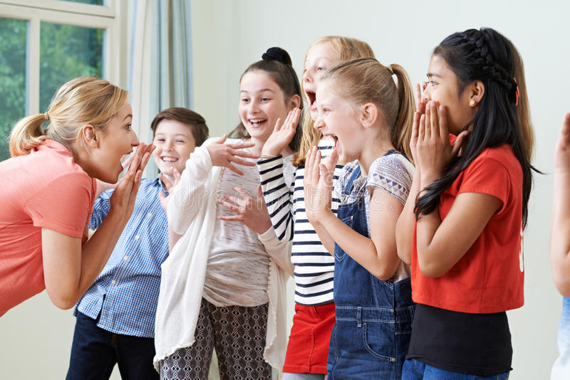 Groupe d'enfants avec le professeur Enjoying Drama Class ensemble image stock