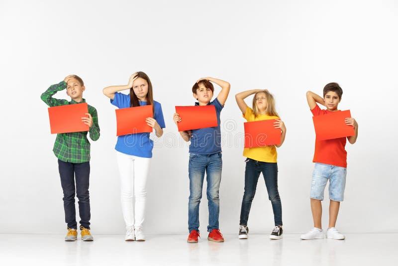 Groupe d'enfants avec les bannières rouges d'isolement dans le blanc photographie stock libre de droits