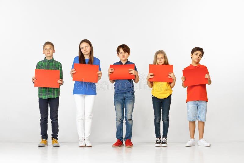 Groupe d'enfants avec les bannières rouges d'isolement dans le blanc photos stock