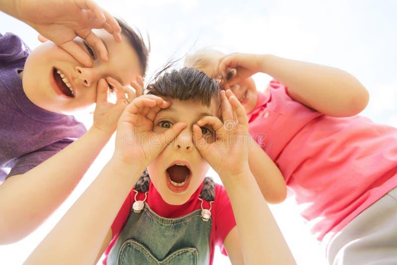 Groupe d'enfants ayant l'amusement et faisant des visages dehors photographie stock