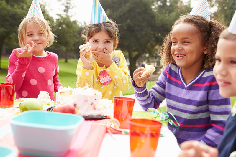 Groupe d'enfants ayant la fête d'anniversaire extérieure photo stock