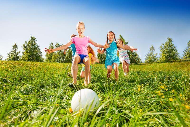Groupe d'enfants courant à la boule dans le pré photographie stock