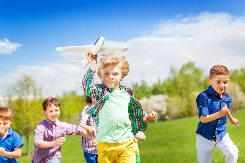 Groupe d'enfants courants heureux avec le jouet d'avion photographie stock