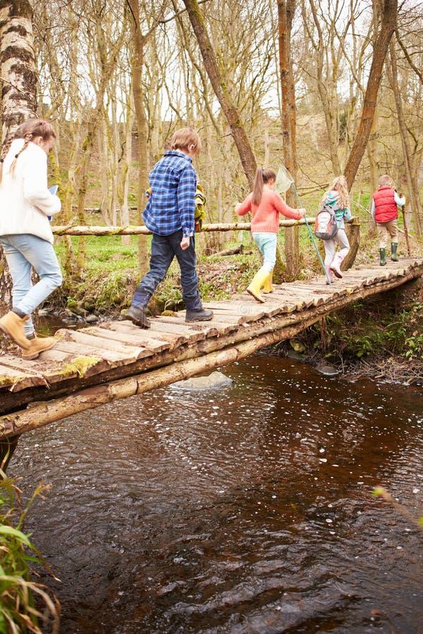 Groupe d'enfants croisant le courant sur le pont en bois photo libre de droits