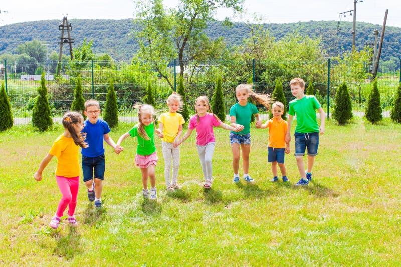 Groupe d'enfants dans des T-shirts colorés extérieurs photos stock