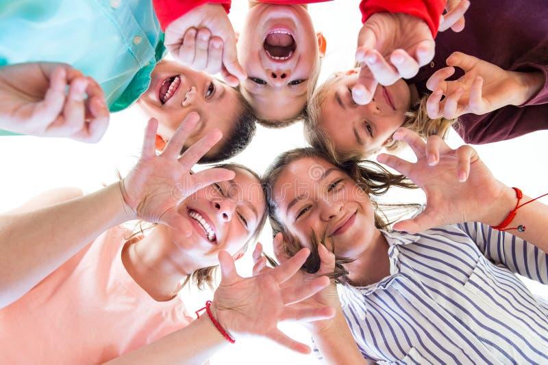Groupe d'enfants de divers âges se tenant en cercle, regardant vers le bas dans la caméra photographie stock