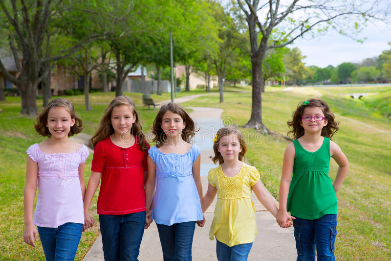 Groupe d'enfants de filles et d'amis de soeurs marchant en parc photo stock