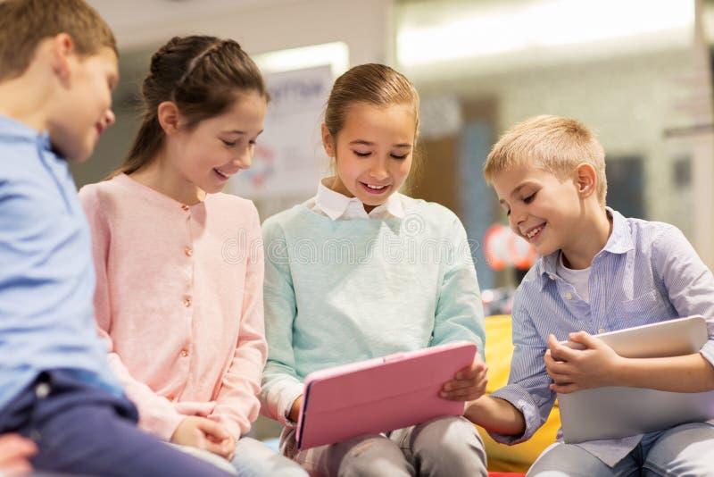 Groupe d'enfants heureux avec le PC de comprimé à l'école image libre de droits