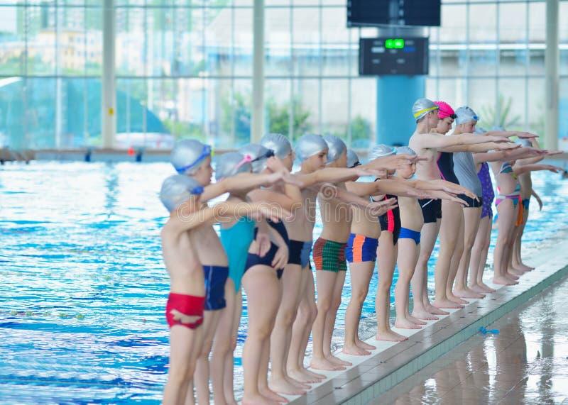 Groupe d'enfants heureux d'enfants à la piscine photographie stock