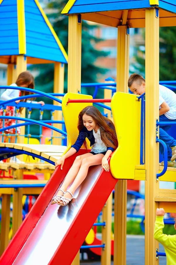 Groupe d'enfants heureux glissant dans le terrain de jeu coloré photographie stock