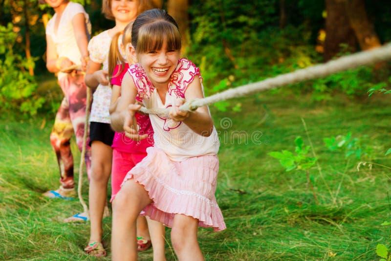 Groupe d'enfants heureux jouant le conflit dehors sur l'herbe Corde de traction d'enfants au parc Colonie de vacances image libre de droits