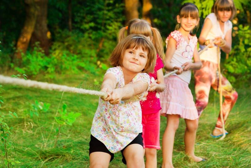 Groupe d'enfants heureux jouant le conflit dehors sur l'herbe Corde de traction d'enfants au parc Colonie de vacances photo libre de droits