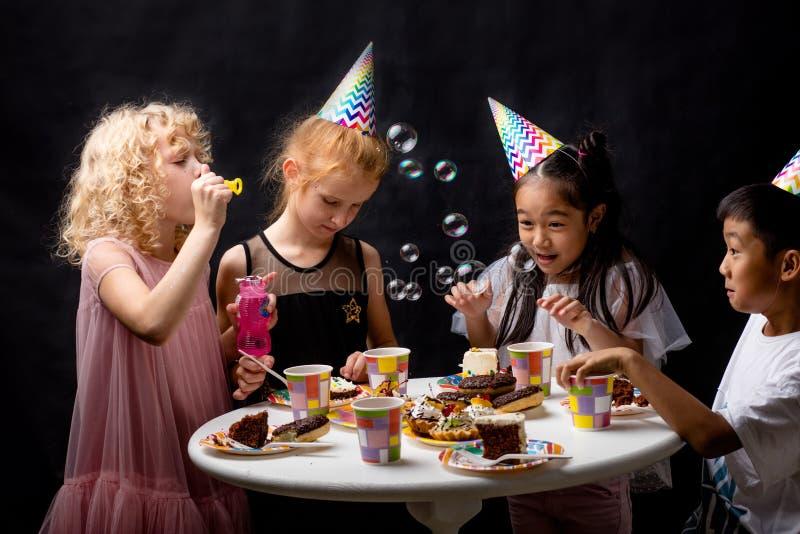 Groupe d'enfants heureux soufflant des bulles de savon pendant l'anniversaire photos libres de droits