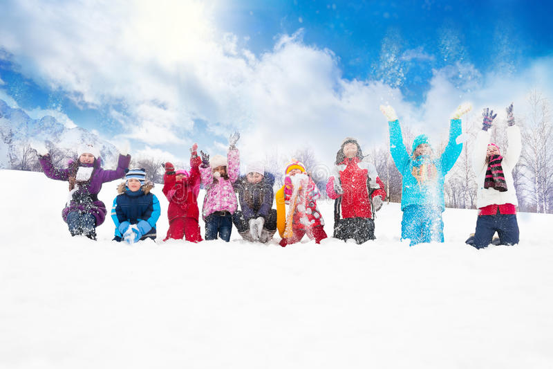 Groupe d'enfants jetant la neige dans le ciel photographie stock libre de droits