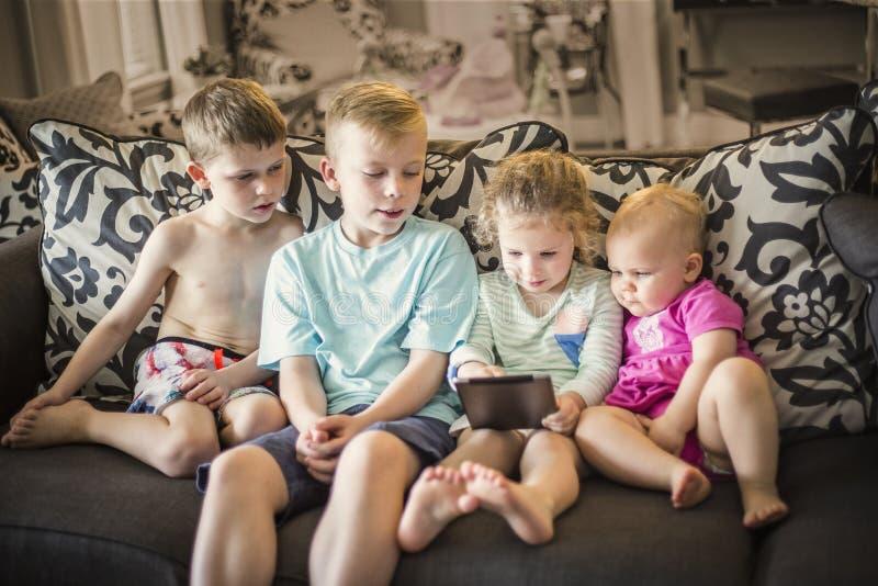 Groupe d'enfants jouant avec les dispositifs électroniques d'un comprimé image stock