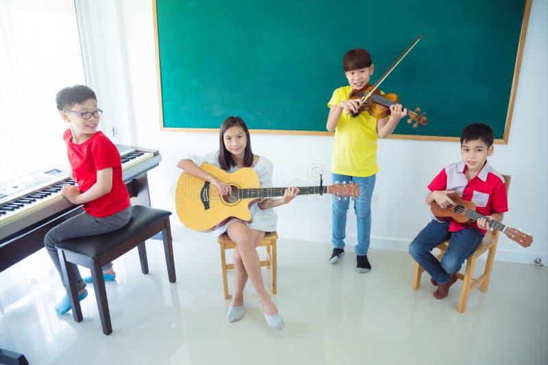 Groupe d'enfants jouant des instruments et le sourire de musique images stock