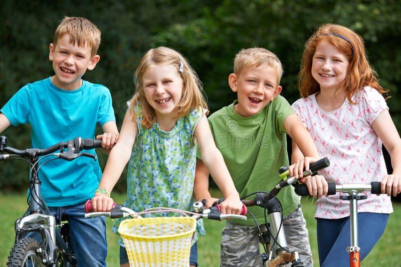 Groupe d'enfants jouant sur les vélos et le scooter images stock