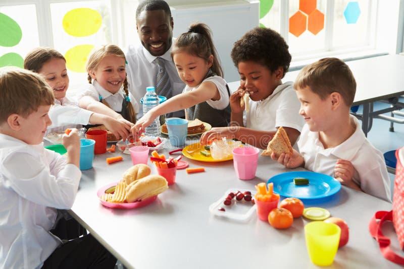 Groupe d'enfants mangeant le déjeuner dans la cafétéria de l'école image stock