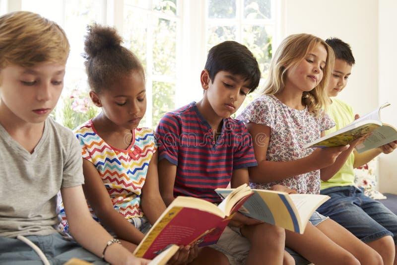 Groupe d'enfants multiculturels lisant sur le siège fenêtre photographie stock libre de droits