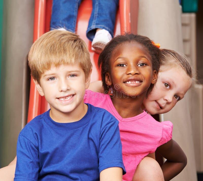 Groupe d'enfants s'asseyant derrière l'un l'autre image libre de droits