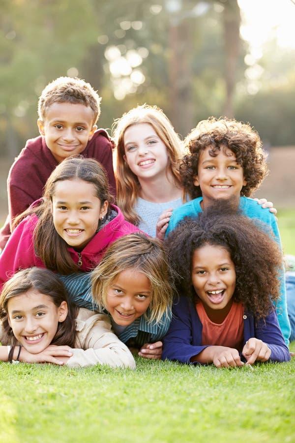 Groupe d'enfants se situant sur l'herbe ensemble en parc images stock