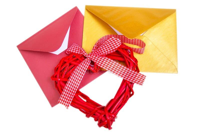 Groupe d'enveloppes multicolores ouvertes avec le coeur en bois rouge photographie stock