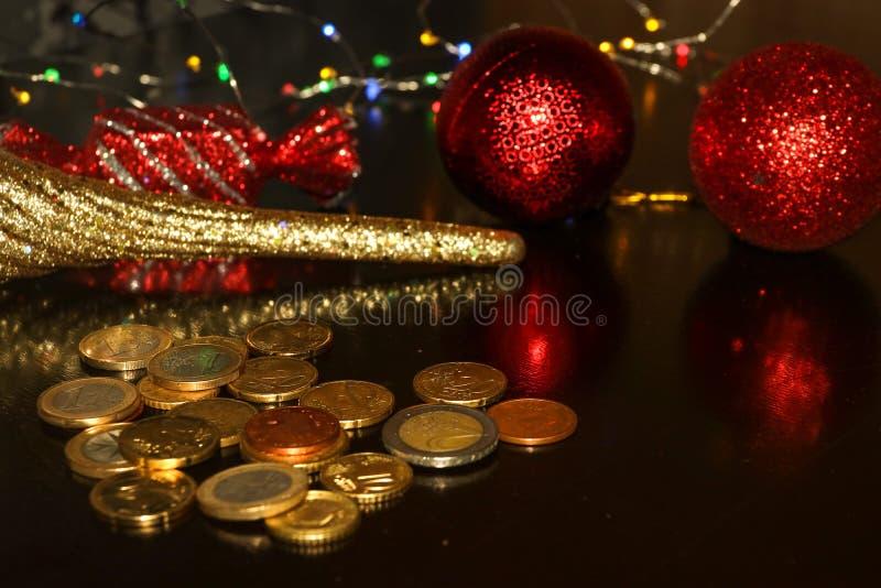 Groupe d'euro pièces de monnaie sur le fond noir avec la réflexion brouillée des jouets de nouvelle année de scintillement image stock