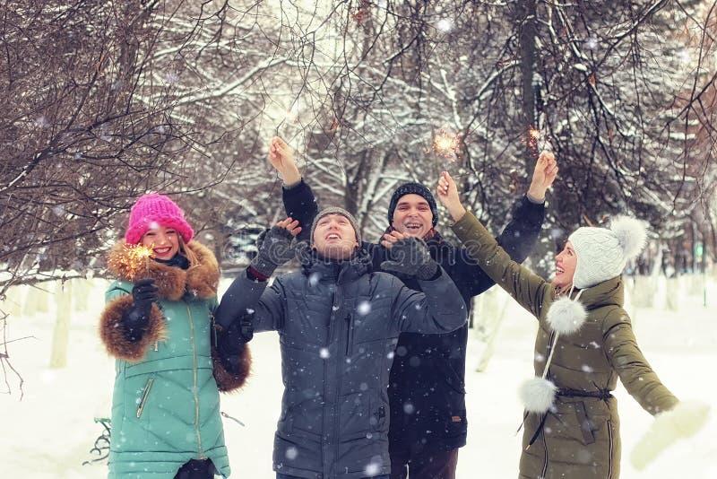 Groupe d'hiver des jeunes avec des cierges magiques image stock