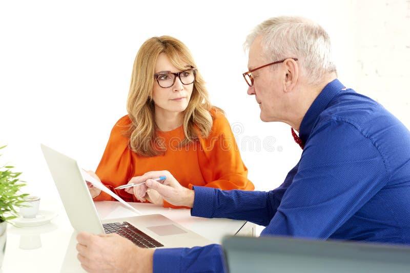 Groupe d'hommes d'affaires à l'aide de l'ordinateur portable tout en travaillant ensemble dans le bureau images stock