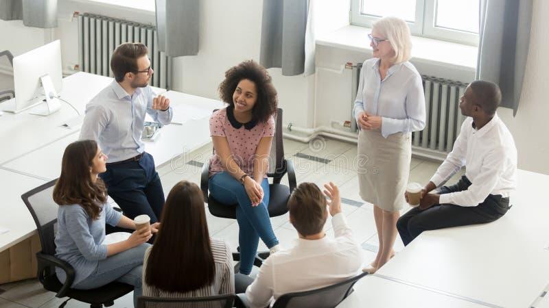 Groupe d'hommes d'affaires discutant le plan de travail avec l'entraîneur à se réunir images libres de droits