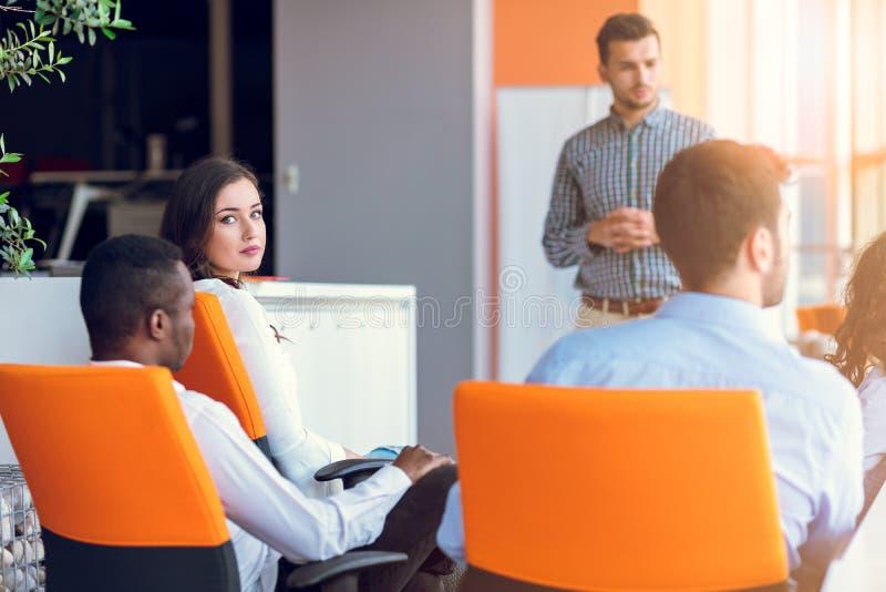 Groupe d'hommes d'affaires en passant habillés discutant des idées dans le bureau photographie stock libre de droits