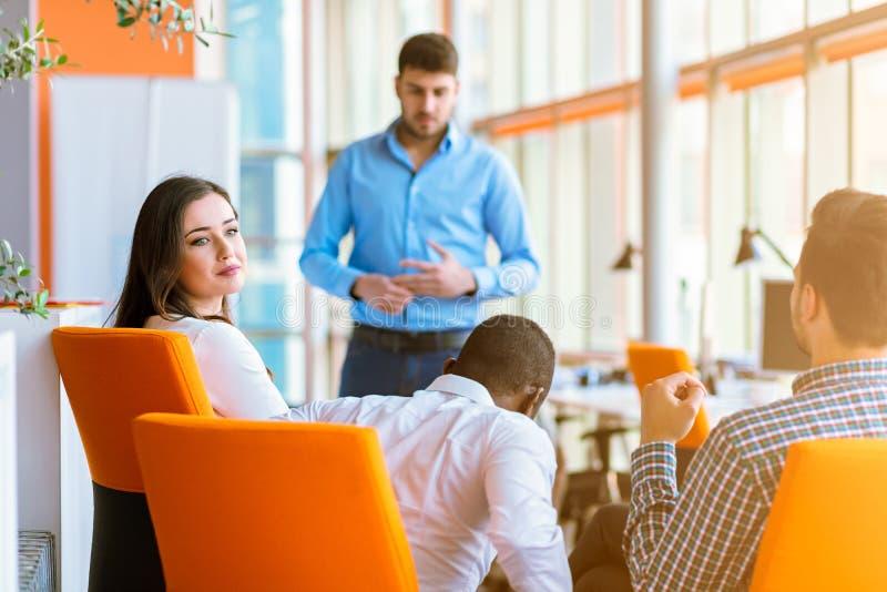 Groupe d'hommes d'affaires en passant habillés discutant des idées dans le bureau image stock