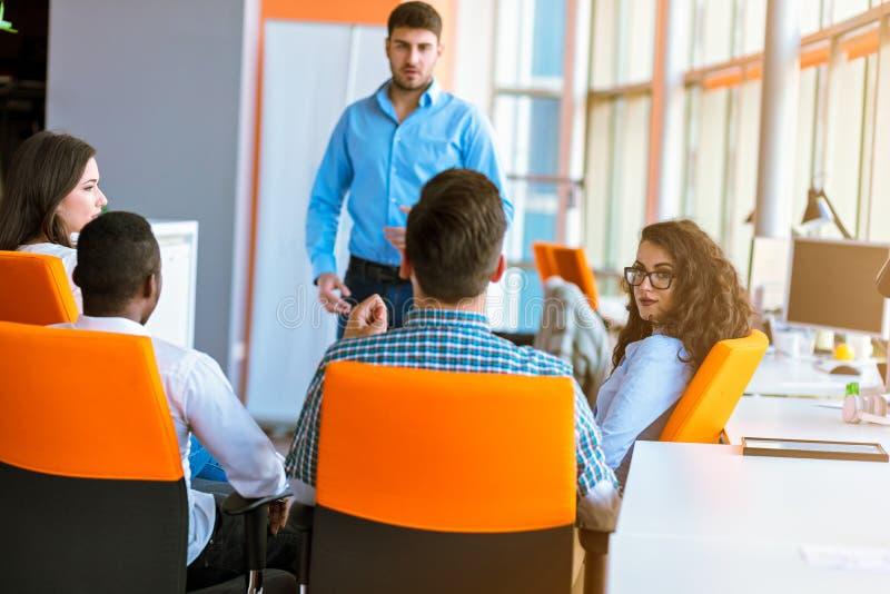 Groupe d'hommes d'affaires en passant habillés discutant des idées dans le bureau images stock