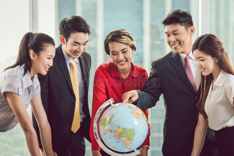 Groupe d'hommes d'affaires regardant le globe images stock