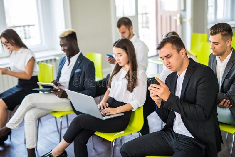 Groupe d'hommes d'affaires s'asseyant dans l'entrevue d'emploi de attente de bureau, plan rapproché Concepts de conférence ou de  image stock