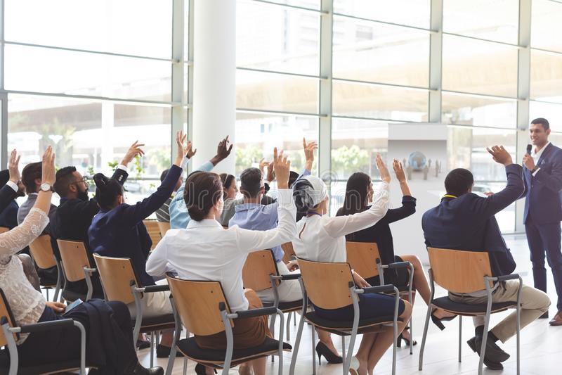 Groupe d'hommes d'affaires soulevant des mains lors du séminaire à la conférence photographie stock libre de droits