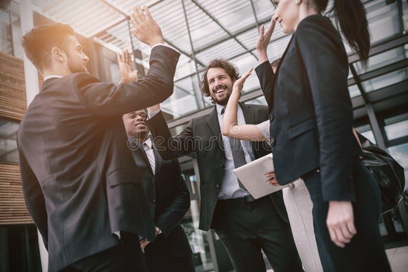 Groupe d'hommes d'affaires heureux donnant la haute cinq entre eux images stock