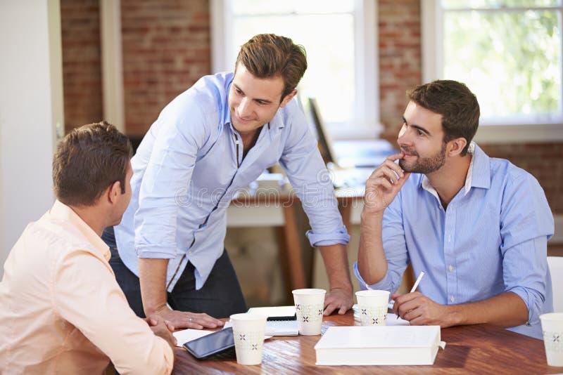 Groupe d'hommes d'affaires se réunissant pour discuter des idées photographie stock