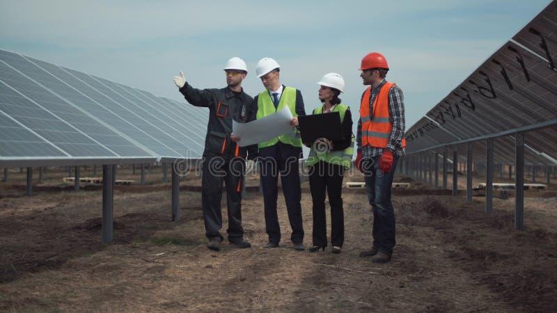 Groupe d'ingénieurs ou de techniciens à une ferme solaire photo stock